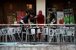 Malaysian forensic officers inspecting the bar in Puchong, the site of the grenade attack last Tuesday in which eight people were injured. Police initially said that a business rivalry or a targeted attack on someone in the pub were the likely motive