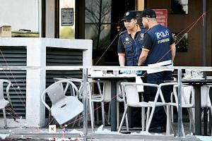 Malaysian forensic experts inspect the site of a grenade attack at a restaurant in the Puchong district outside Kuala Lumpur.