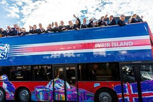 The Iceland national football team arrives in Reykjavik on July 4, 2016, on a bus while people in the streets greet them.