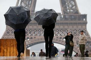 Tourists stroll on the Trocadero square, in front of the Eiffel Tower during a rainy day in Paris on May 30, 2016.