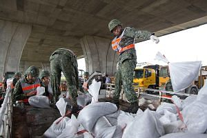 Soldiers distributing sand bags to residents in Ilan county in north-east Taiwan yesterday. More than 35,000 soldiers are on standby to help with evacuations and disaster relief.