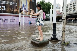 A woman emptying water out of her boot in Wuhan, which received in a week almost as much rain as London gets in a year.