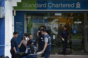 Police officers and investigators from the Criminal Investigation Department at the Standard Chartered Bank branch in Holland Village after the robbery yesterday. The suspect, described as a Caucasian man wearing a grey hoodie and mustard trousers, m
