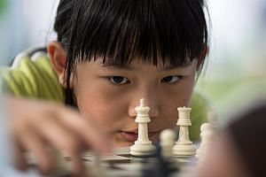 A young girl pondering her next move during an outdoor chess activity at the Central Harbourfront in Hong Kong. Many grown-up Hong Kongers are reportedly also weighing their next step: To remain in Hong Kong or emigrate to another country?