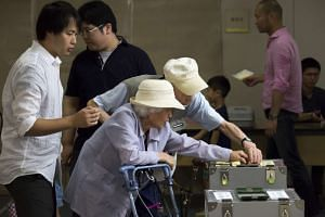 Voters cast their ballots for the upper house election at a polling station in Tokyo, Japan, on July 10.