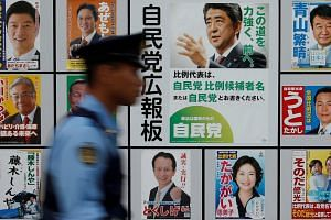 A police officer walks past Japan's ruling Liberal Democratic Party's poster at the LDP headquarters in Tokyo, Japan on July 10, 2016.