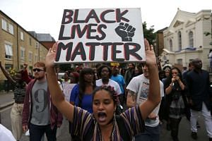 """A women holds up a  """"Black Lives Matter"""" placard as people march in Brixton, south London to protest against police brutality in the US on Saturday."""