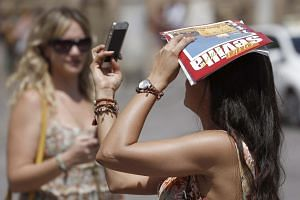 A tourist takes a photo as she covers her head with a tourist guide near the cathedral in the city of Seville, southern Spain, July 2.