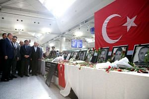 Turkish President Tayyip Erdogan looks at pictures of Ataturk airport employees who were killed in the attack, during his visits to Ataturk airport, on July 2, 2016.