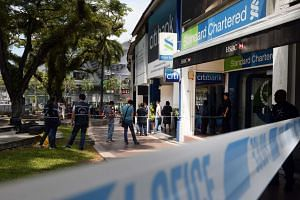 Security tape was put up around the perimeter of the Standard Chartered Bank at Holland Village following a robbery on Thursday (July 7).