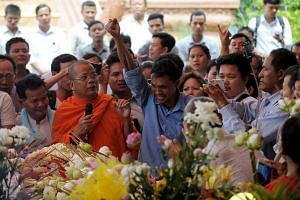 A Cambodian mourner raises his arm as he pays his respects at the funeral ceremony of political analyst Kem Ley in Phnom Penh, on July 11, 2016.