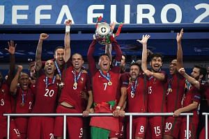 Cristiano Ronaldo (centre) lifts the trophy after winning the Uefa Euro 2016 final match between Portugal and France.