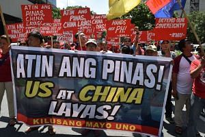 Activists carrying anti-China and US placards march towards the Chinese consulate in a protest in Manila, on July 12, 2016.
