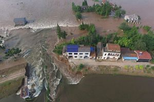 Houses are flooded as a dike breaches in Huarong County, Hunan Province on July 10, 2016.