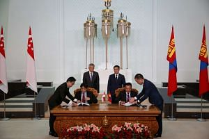 Prime Minster Lee Hsien Loong and Mongolian Prime Minister Jargaltulga Erdenebat witness the MOU signing between the Singapore Cooperation Enterprise and the Mongolian Energy Development Centre.