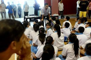 A teacher speaks to pupils before the PSLE results are handed out at Eunos Primary School on Nov 25, 2015.