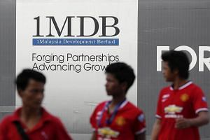 Men walk past a 1MDB billboard at the fund's flagship Tun Razak Exchange development in Kuala Lumpur.