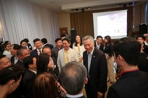 PM Lee meeting Singaporeans at a reception in Mongolia. Businessmen from Singapore and Mongolia, as well as Mongolians who had studied in Singapore, were also at the reception.