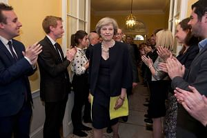 Staff applaud as Britain's new PM Theresa May, and her husband Philip, walk into 10 Downing Street after Mrs May had met Queen Elizabeth in Buckingham Palace, in central London, Britain, on July 13.