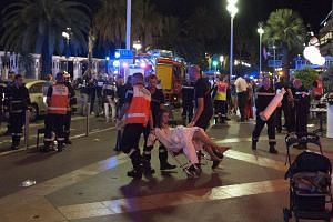 Wounded people are evacuated from the scene where a truck crashed into the crowd during the Bastille Day celebrations in Nice, France, July 14.