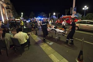 Wounded people are evacuated from the scene where a truck crashed into the crowd during the Bastille Day celebrations in Nice, France on July 14.