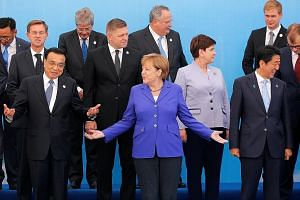 German Chancellor Angela Merkel (in blue) gesturing between Chinese Premier Li Keqiang (left) and Japanese Prime Minister Shinzo Abe as they posed with other heads of delegations for a group photo during the Asia-Europe Meeting in Ulaanbaatar, Mongol