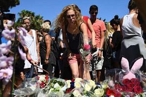 A woman lays a flower in the street of Nice to pay tribute to the victims on July 15, 2016.