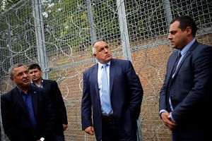 Bulgarian Prime Minister Boiko Borisov (centre) inspects the barbed wire fence constructed on the Bulgarian-Turkish border, near Malko Tarnovo, Bulgaria, May 22, 2016.