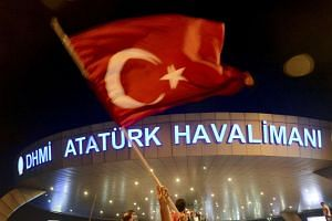 A man waves a Turkish flag in front of Ataturk Airport during an attempted coup in Istanbul, Turkey July 16, 2016.