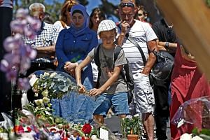 People gather in front of a memorial set up on the Promenade des Anglais where the truck ploughed into the crowd.