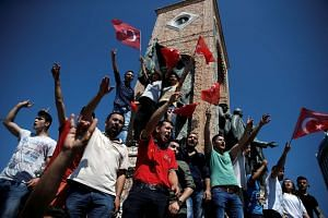 Supporters of Turkish President Tayyip Erdogan wave Turkish national flags in Istanbul's Taksim Square on July 16, 2016.