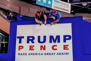 Workers hanging a campaign sign inside the Quicken Loans Arena, the site of the 2016 Republican National Convention in Cleveland, Ohio on July 17.
