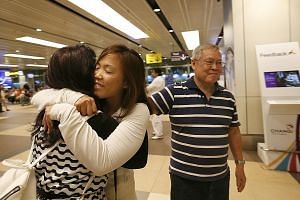 Ms Grace Feng, 33, hugging her mother, Madam Mary Lan, 66, at Changi Airport on her return from Turkey yesterday. Beside her is her father, Mr Philip Feng, 68. Several Singaporeans in Turkey resumed their journeys or arrived home last night. SEE TOP