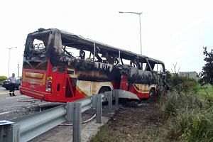 Investigators inspect a bus carrying tourists from mainland China that crashed and caught fire along an expressway, on July 19, 2016.