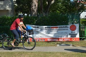 A man cycles past a dengue alert banner.