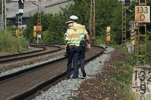 Police officers walk along the track in Wuerzburg, Germany, on July 19, 2016, a day after a man attacked passengers on a train with an axe.