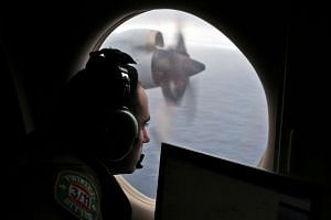 A flight officer looks out of a Royal Australian Air Force AP-3C Orion as it flies over the southern Indian Ocean in a search for the missing MH370, on March 22, 2014.