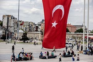 Locals and visitors sit beneath a giant Turkish national flag on Taksim Square in Istanbul, Turkey.