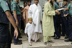 Security officials at the entrance of a mosque in Dhaka check people through a metal detector during Friday prayers. The country's anti-militancy operation shows that the government appears to have moved from denial mode and is taking the threat of extrem