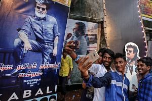 Fans of superstar Rajinikanth taking a photo with his posters as they celebrate the opening of his film Kabali at Aurora theatre in Mumbai.