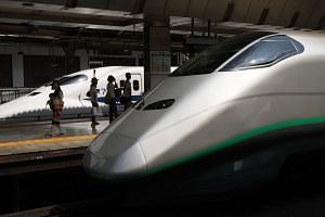An East Japan Railway Co. Shinkansen bullet train (right) and a Central Japan Railway Co. Shinkansen bullet train sit on the platform of Tokyo Station, in Tokyo, Japan, in 2011.