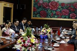 Myanmar State Counsellor and Foreign Minister Aung San Suu Kyi (left) talks during the bilateral meeting with Chinese Foreign Minister Wang Yi (centre right) in Vientiane, Laos on July 24.