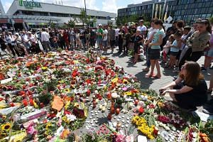 Candles and flowers left yesterday at a makeshift memorial at the Olympia shopping centre in the German city of Munich to remember the nine victims of a shooting rampage last Friday. Officials said the 18-year-old gunman had been planning his crime f