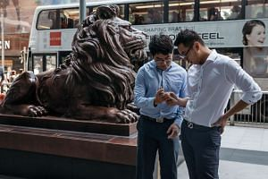 Office workers play Pokemon Go on their smartphones outside the HSBC Holdings Plc headquarters building in Hong Kong.