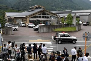 Journalists gather at the main gate of the Tsukui Yamayuri En care centre in Sagamihara, Kanagawa prefecture, on July 26, 2016.