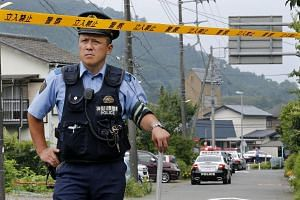 A Japanese police officer blocks the road leading to a residential care facility for disabled people in Sagamihara, Tokyo.