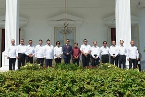 Indonesian President Joko Widodo (seventh from left) and Vice-President Jusuf Kalla (seventh from right) pose with the new members of his cabinet at the presidential palace in Jakarta on July 27, 2016.