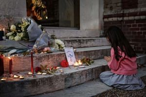 A girl prays at a makeshift memorial in front of the city hall after a fatal hostage-taking incident at the church in Saint-Etienne-du-Rouvray, France on July 26, 2016.