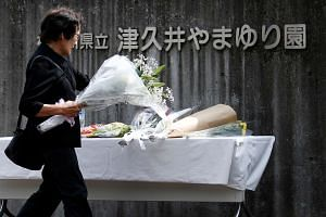 A woman offering flowers at a memorial to victims of a knife attack, outside the facility for the disabled in Sagamihara where the attack took place, on July 27, 2016.