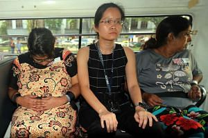 A CID officer sits between Gaiyathiri Murugayan (left) and her mother Prema Naraynasamy, who were charged in court on Thursday (July 28) with murdering their Myanmar domestic worker at their home in Bishan earlier this week.